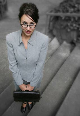 Young woman in a suit with a briefcase, looking eager to work