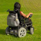 person in wheelchair riding across grassy field